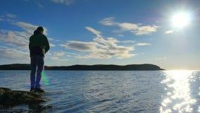 A linha de pesca da verificação do pescador e empurrão da isca na haste, prepara-se e joga-se a atração distante na água calma O  video estoque