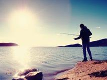 A linha de pesca da verificação do pescador e empurrão da isca na haste, prepara-se e joga-se a atração distante na água calma Imagem de Stock