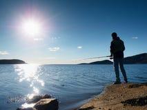 A linha de pesca da verificação do pescador e empurrão da isca na haste, prepara-se e joga-se a atração distante na água calma Fotos de Stock