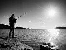 A linha de pesca da verificação do pescador e empurrão da isca na haste, prepara-se e joga-se a atração distante na água calma Imagens de Stock Royalty Free