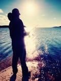 A linha de pesca da verificação do pescador e empurrão da isca na haste, prepara-se e joga-se a atração distante na água calma Fotos de Stock Royalty Free