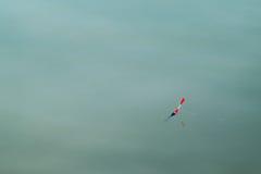 A linha de pesca do flutuador na água imagens de stock