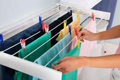 Linha de roupa de Person Hanging Wet Cloth On fotos de stock royalty free