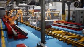Linha de soldadura do carro de transporte com estruturas de carros inacabados e de soldadores dos robôs vídeos de arquivo