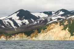 Linha de surpresa da costa com as rochas coloridas amarelas alaranjadas da pedra calcária da areia e as estruturas na costa, expe foto de stock