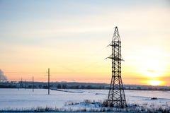 Linha de transmissão de alta tensão no inverno no por do sol fotos de stock