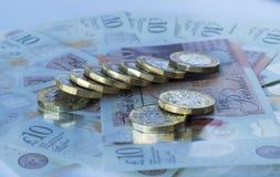 Linha diagonal de moedas de libra novas em dez notas da libra Fotografia de Stock