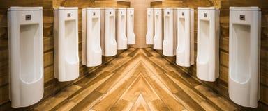 Linha dos mictórios brancos da porcelana em toaletes públicos limpos, claros fotografia de stock