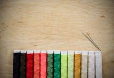 Linha e agulhas de costura no fundo de madeira Foto de Stock Royalty Free