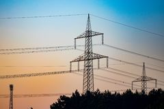 Linha eléctrica do pilão e da transmissão no por do sol fotos de stock royalty free