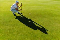 Linha masculina da verificação do jogador de golfe para pôr a bola de golfe Fotografia de Stock