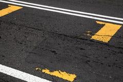 Linhas amarelas e brancas sobre o asfalto escuro imagens de stock