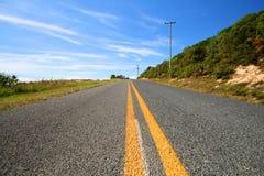 Linhas amarelas em uma estrada reta Fotografia de Stock