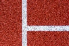 Linhas brancas em uma superfície vermelha da textura da pista de atletismo, backgrou Imagens de Stock Royalty Free