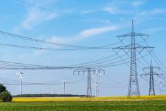 Linhas de abastecimento do poder e algumas turbinas eólicas Foto de Stock
