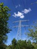 Linhas de alta tensão e nuvens nas árvores Imagens de Stock Royalty Free