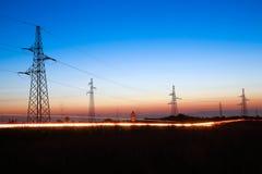 Linhas de alta tensão elétricas no crepúsculo Fotos de Stock Royalty Free