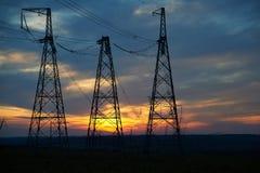 Linhas de alta tensão elétricas sobre o nascer do sol Fotos de Stock Royalty Free