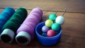 Linhas de costura coloridas com bolhas coloridas no fundo de madeira Imagens de Stock