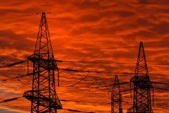 Linhas de transmissão da energia eléctrica no por do sol Fotografia de Stock