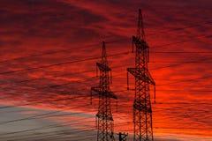 Linhas de transmissão da energia eléctrica no por do sol Foto de Stock Royalty Free