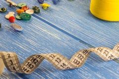 Linhas dos botões e da fita do centímetro em um fundo de madeira azul fotos de stock royalty free