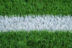 Linhas dos esportes pintadas em um campo de ação gramíneo verde imagens de stock