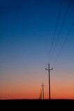 Linhas eléctricas elétricas na laranja do vermelho azul do por do sol Imagem de Stock