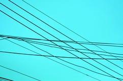 Linhas elétricas de entrecruzamento no fundo azul Fotos de Stock Royalty Free