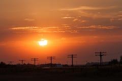 Linhas elétricas mostradas em silhueta no por do sol dourado Imagem de Stock