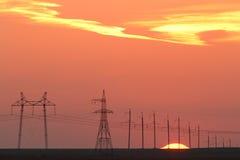 Linhas elétricas na perspectiva de um por do sol bonito Fotos de Stock Royalty Free