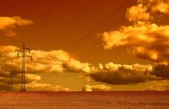 Linhas elétricas que correm através de um campo de trigo no por do sol Imagem de Stock
