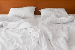 Linho branco amarrotado da cama na manhã ao hotel Fotografia de Stock