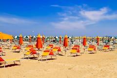 Linia brzegowa z pomarańczowymi parasolami i niebieskim niebem Fotografia Stock