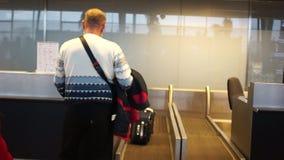 Linia lotnicza pasażer w lotnisku Tylni widok mężczyzna sprawdza wewnątrz dla lota przy lotniskiem, sprawdzać w jego bagażu zbiory wideo