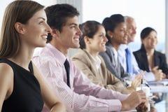 Linia ludzie biznesu Słucha prezentacja Sadzająca Przy Szklanym sala posiedzeń stołem Zdjęcia Stock