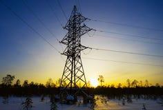 Linie der Elektrizitätsübertragung im Winter bei Sonnenuntergang Lizenzfreie Stockbilder