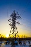 Linie der Elektrizitätsübertragung im Winter bei Sonnenuntergang Lizenzfreie Stockfotografie