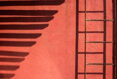Linie des Schattens auf einer roten Wand Stockfotografie