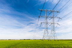 Linie energetyczne i pilony w wiejskim krajobrazie Fotografia Stock