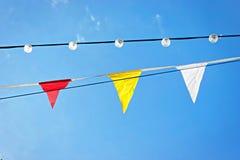 Linie von bunten Festivalflaggen und -lampen gegen blauen Himmel Stockfotografie