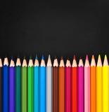 Linie von bunten hölzernen Bleistiften auf Schwarzem Lizenzfreies Stockfoto