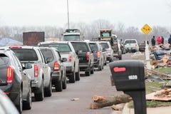 Linie von den Autos, die in eine zerstörte Nachbarschaft strömen Stockbild