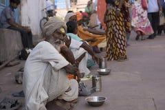 Linie von den Bettlern, die außerhalb eines Tempels in Indien sitzen stockfoto