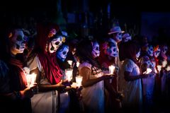 Linie von den customed Frauen, die als Catrinas mit Schädelmake-up gekleidet wurden und von Kerzen glänzte durch Blaulicht am Ere stockfotografie