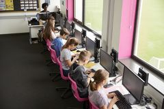 Linie von den hohen Schülern, die an den Schirmen in der Computer-Klasse mit weiblichem Lehrer In Background Shot vom hohen Winke lizenzfreie stockfotografie