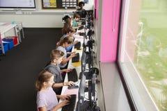 Linie von den hohen Schülern, die an den Schirmen in der Computer-Klasse mit weiblichem Lehrer In Background Shot vom hohen Winke stockfoto