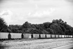 Linie von Frachtwaggons entlang einer Landstraße Stockfotografie