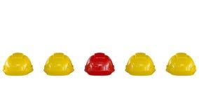 Linie von gelben Schutzhelmen mit einem roten  Lizenzfreie Stockbilder