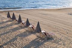 Linie von geschlossenen Strandschirme lougners, Stühlen und sunbeds Stockbilder